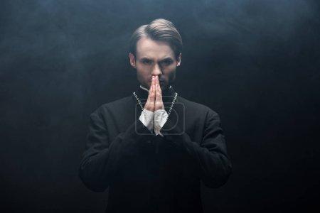 Photo pour Prêtre catholique sérieux regardant la caméra tout en priant sur fond noir avec de la fumée - image libre de droit