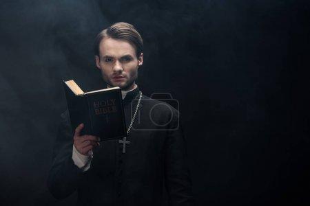 Photo pour Jeune prêtre catholique sérieux regardant la caméra tout en lisant la bible sur fond noir avec de la fumée - image libre de droit