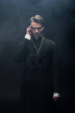Photo pour Jeune prêtre catholique réfléchi toucher la tête tout en regardant la caméra sur fond noir avec de la fumée - image libre de droit