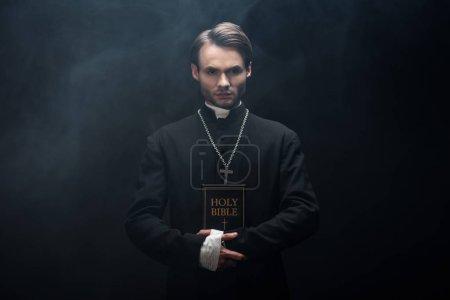 Photo pour Jeune prêtre catholique confiant regardant la caméra tout en tenant la bible sainte sur fond noir avec de la fumée - image libre de droit