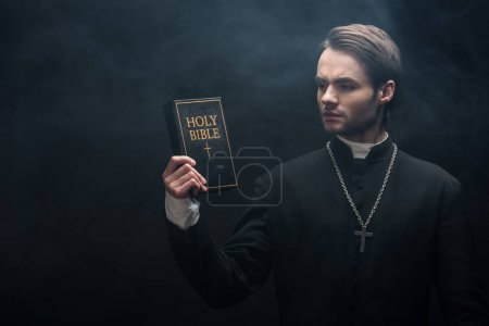 pensativo sacerdote católico mirando la sagrada biblia sobre fondo negro con humo