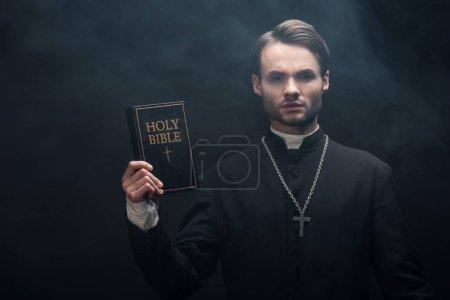 Photo pour Jeune prêtre catholique sérieux montrant la bible sainte à la caméra sur fond noir avec de la fumée - image libre de droit
