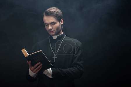 attentive catholic priest reading holy bible on black background with smoke