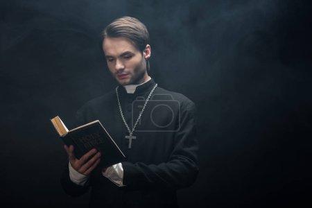 Photo pour Prêtre catholique attentif lisant la bible sainte sur fond noir avec de la fumée - image libre de droit