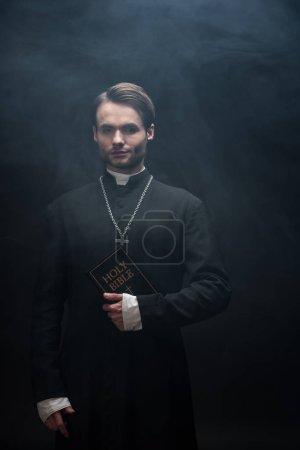 Photo pour Prêtre catholique confiant tenant sainte bible et regardant la caméra sur fond noir avec de la fumée - image libre de droit