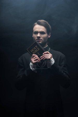 Photo pour Prêtre catholique tendu regardant la caméra tout en tenant la bible sainte sur fond noir avec de la fumée - image libre de droit