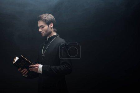 Photo pour Prêtre catholique concentré lisant la bible sainte sur fond noir avec de la fumée - image libre de droit