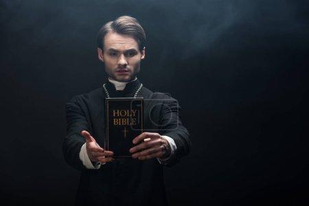 Photo pour Prêtre catholique confiant tenant la bible sainte dans la main tendue sur fond noir avec de la fumée - image libre de droit