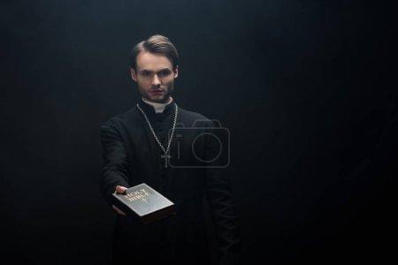 Photo pour Jeune prêtre catholique sérieux tenant la bible sainte dans la main tendue isolé sur noir - image libre de droit