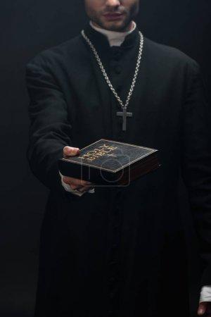 abgeschnittene Ansicht eines katholischen Priesters, der die heilige Bibel in ausgestreckter Hand hält, isoliert auf schwarz
