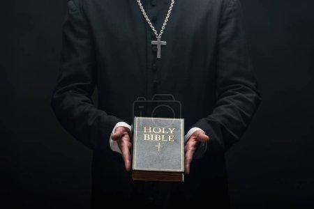 Photo pour Vue recadrée du prêtre catholique tenant la bible sainte isolée sur noir - image libre de droit