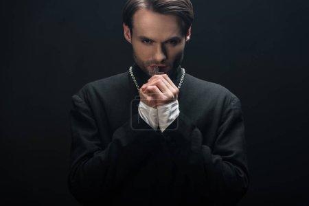 Photo pour Jeune prêtre catholique réfléchi tenant croix d'argent sur son collier isolé sur noir - image libre de droit
