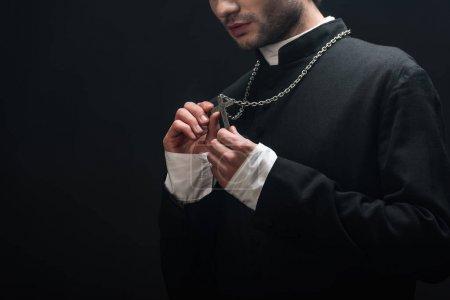 Photo pour Vue recadrée du prêtre catholique regardant la croix d'argent sur son collier isolé sur noir - image libre de droit