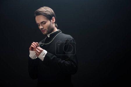 Photo pour Jeune prêtre catholique sérieux regardant la croix d'argent sur son collier isolé sur noir - image libre de droit