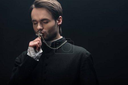 Photo pour Jeune prêtre catholique réfléchi embrassant croix d'argent avec les yeux fermés isolé sur noir - image libre de droit
