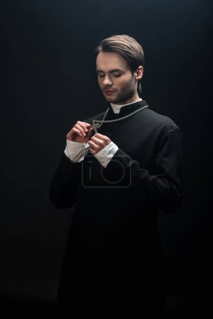 Photo for Young thoughtful catholic priest looking at silver cross on his necklace isolated on black - Royalty Free Image