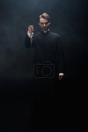 Photo pour Vue pleine longueur du prêtre catholique confiant tenant collier avec croix sur fond noir avec de la fumée - image libre de droit