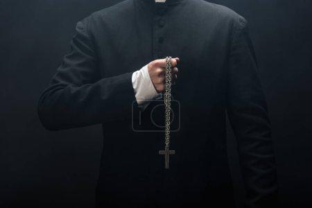 Photo pour Vue recadrée du prêtre catholique tenant collier avec croix d'argent isolé sur noir - image libre de droit