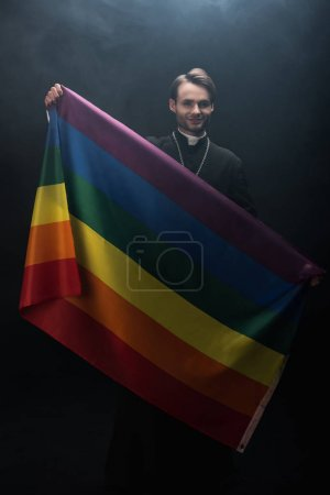 Photo for Smiling catholic priest holding lgbt flag while looking at camera on black background with smoke - Royalty Free Image