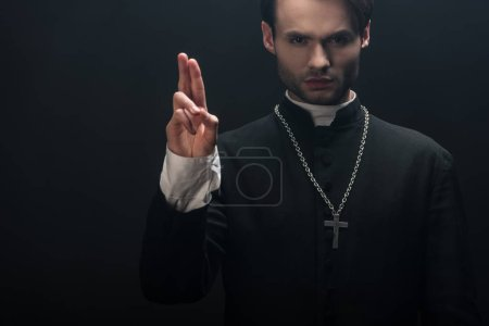 Photo pour Jeune prêtre catholique confiant regardant la caméra et montrant un geste de bénédiction isolé sur noir - image libre de droit