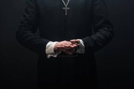 Photo pour Recadré de prêtre catholique debout avec les mains pliées isolé sur noir - image libre de droit