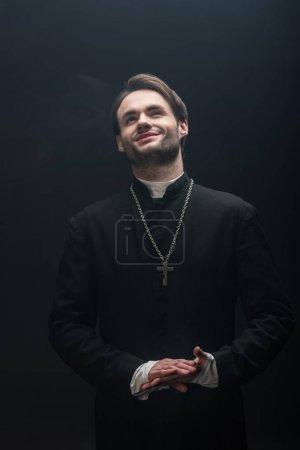 Photo pour Heureux prêtre catholique debout avec les mains pliées et regardant vers le haut isolé sur noir - image libre de droit