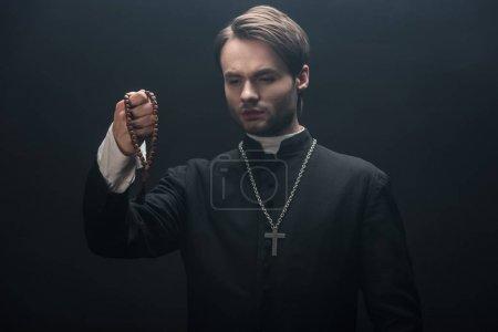 Photo pour Jeune prêtre catholique tendu regardant des perles de chapelet en bois isolé sur noir - image libre de droit