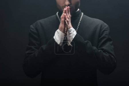 Photo for Cropped view of young catholic priest praying isolated on black - Royalty Free Image
