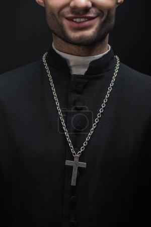 Photo pour Vue recadrée du prêtre catholique souriant avec croix d'argent sur collier isolé sur noir - image libre de droit