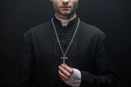 levágott kilátás katolikus pap megérinti ezüst kereszt elszigetelt fekete