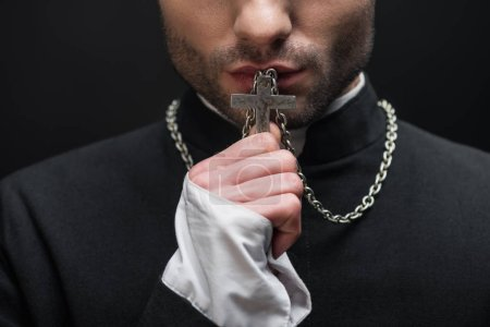 cropped view of catholic priest kissing silver cross on his necklace isolated on black