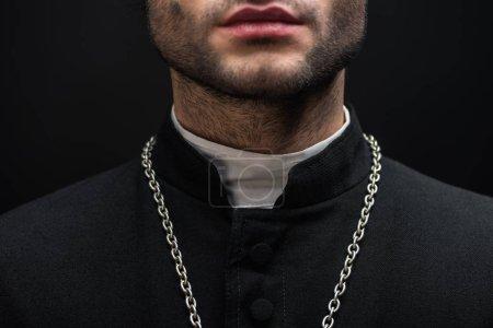 Photo pour Vue recadrée du prêtre catholique en soutane noire avec collier en argent isolé sur noir - image libre de droit
