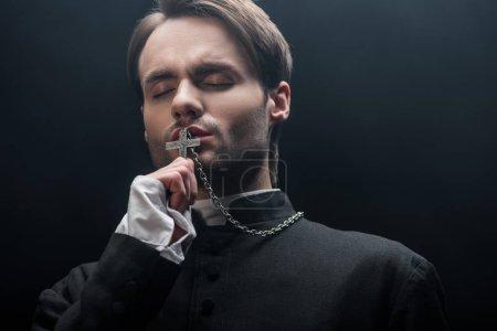 Photo pour Vue de bas angle de jeune prêtre catholique réfléchi embrassant croix avec les yeux fermés isolé sur noir - image libre de droit