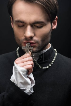 Photo pour Jeune prêtre catholique réfléchi baisers croix avec les yeux fermés isolé sur noir - image libre de droit