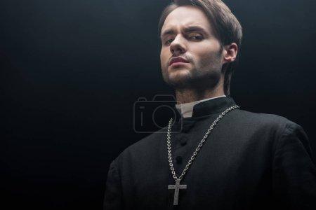 Photo pour Vue à angle bas du jeune prêtre catholique tendu regardant la caméra isolée sur noir - image libre de droit