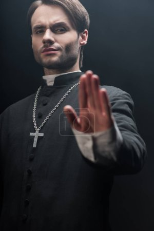 low angle view of strict catholic priest showing refuse gesture isolated on black