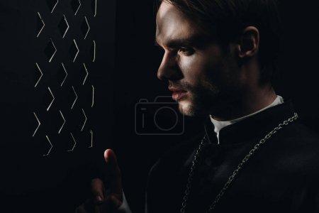 Photo pour Jeune prêtre catholique tendu regardant à travers la calandre confessionnelle dans l'obscurité avec des rayons de lumière - image libre de droit