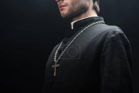 Photo pour Vue recadrée du prêtre catholique en soutane noire avec croix d'argent sur collier isolé sur noir - image libre de droit