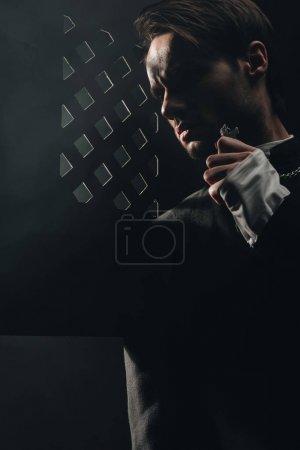 Photo pour Jeune prêtre catholique sérieux touchant croix sur son collier dans l'obscurité près de calandre confessionnelle - image libre de droit