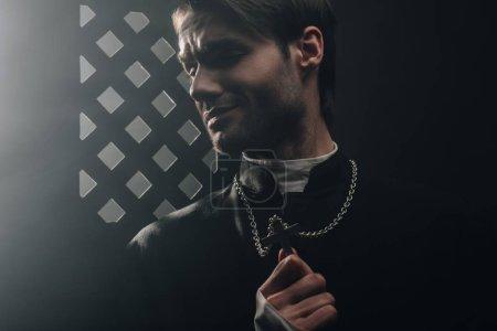Photo pour Jeune prêtre catholique inquiet touchant croix sur son collier dans l'obscurité près de calandre confessionnelle - image libre de droit