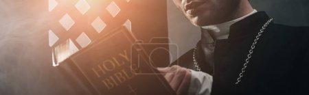 Photo pour Vue recadrée du prêtre catholique lisant la Bible dans l'obscurité près de la calandre confessionnelle avec des rayons de lumière, prise de vue panoramique - image libre de droit
