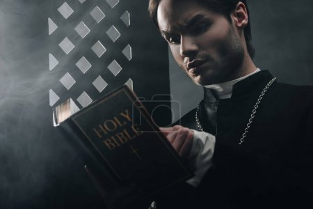 young thoughtful catholic priest reading bible near confessional grille in dark with rays of light
