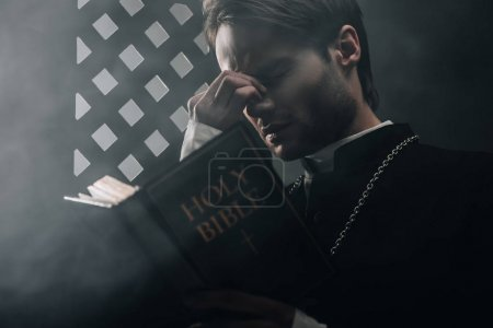 Photo for Young thoughtful catholic priest touching face while reading bible near confessional grille in dark with rays of light - Royalty Free Image