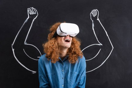 Photo for Excited girl using virtual reality headset with strong arms drawing on blackboard - Royalty Free Image