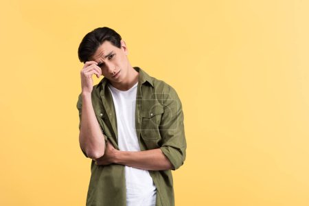 Photo for Thoughtful brunette young man, isolated on yellow - Royalty Free Image