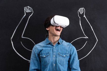excited young man using virtual reality headset, with muscular arms drawing on chalkboard