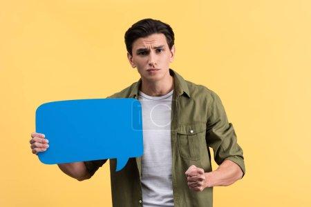 Photo pour Homme agressif tenant poing et bulle de parole bleue, isolé sur jaune - image libre de droit