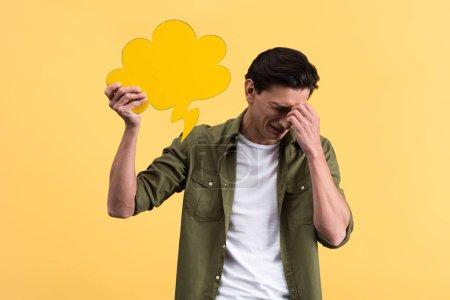 crying man holding cloud speech bubble, isolated on yellow