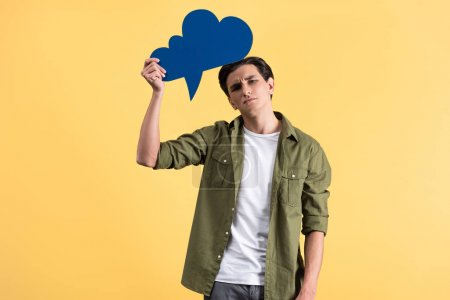 Photo for Emotional sad man holding blue cloud speech bubble, isolated on yellow - Royalty Free Image