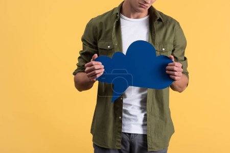 Photo for Cropped view of man holding blue cloud speech bubble, isolated on yellow - Royalty Free Image